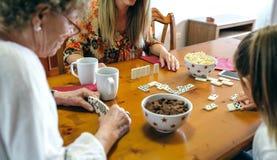 3 женского поколения играя домино Стоковая Фотография