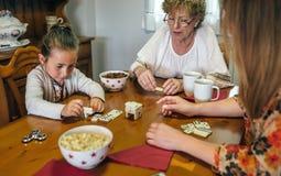 3 женского поколения играя с домино Стоковые Изображения