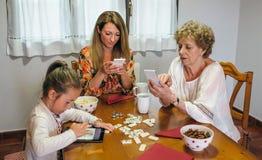 3 женского поколения используя таблетку и smartphone Стоковые Изображения RF