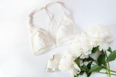 Женское бельё женщины с аксессуарами и коллажем цветков на белизне, плоском положении, взгляд сверху Стоковые Фотографии RF