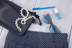 Женское вещество моды - сумка, брюки, солнечные очки, маникюр, ювелирные изделия жемчуга на деревянной предпосылке стоковое фото