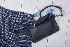 Женское вещество - сумка, брюки, солнечные очки, маникюр на белой деревянной предпосылке стоковая фотография rf