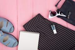 Женское вещество - сумка, брюки, солнечные очки, маникюр, сандалии, пустой блокнот на розовой деревянной предпосылке стоковое изображение