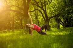 Женское делая представление планки стороны asana йоги с изогнутой ногой Стоковое Фото