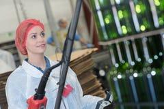 Женское заводской рабочий в проверять разливая по бутылкам индустрии Стоковое Изображение RF