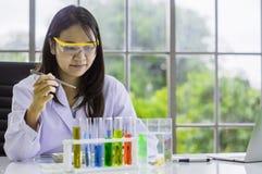 Женское здравоохранение ученого работая в химической лаборатории, с красочными химическими бутылками и трубками помещенными на та стоковое фото