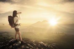 Женское использование hiker бинокулярное в скале Стоковые Изображения