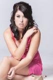 Женское модельное усаживание с серой предпосылкой Стоковая Фотография