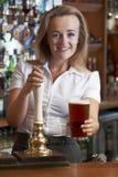 Женское питье сервировки бармена к клиенту Стоковые Изображения