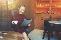 женское смотря кино на сенсорной панели пока завтрак в кофейне Стоковое Фото