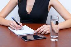 Женское сочинительство руки с ручкой на таблице рядом с smartphone Стоковое фото RF