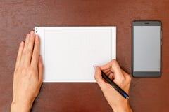 Женское сочинительство руки с ручкой на таблице рядом с smartphone Стоковые Изображения RF