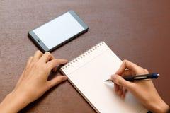 Женское сочинительство руки с ручкой на таблице рядом с smartphone Стоковые Изображения