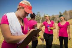 Женское сочинительство тренера на доске сзажимом для бумаги в лагере ботинка Стоковые Фото