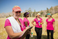 Женское сочинительство тренера на доске сзажимом для бумаги в лагере ботинка Стоковые Изображения RF