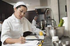 Женское сочинительство шеф-повара на доске сзажимом для бумаги в кухне стоковые изображения rf