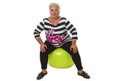 Женское старшее усаживание на швейцарском шарике Стоковые Изображения