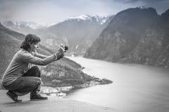 Женское туристское принимая фото на норвежском фьорде Стоковое Изображение