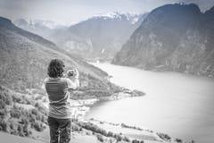 Женское туристское принимая фото на норвежском фьорде Стоковое Изображение RF