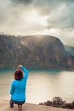 Женское туристское принимая фото на норвежском фьорде Стоковые Изображения RF