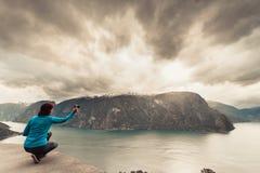 Женское туристское принимая фото на норвежском фьорде Стоковые Фотографии RF