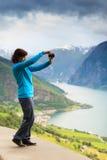 Женское туристское принимая фото на норвежском фьорде Стоковые Фото