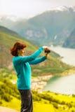 Женское туристское принимая фото на норвежском фьорде Стоковая Фотография