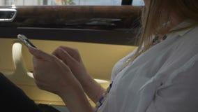 Женское усаживание на заднем сиденье дорогого автомобиля, принимая мобильный телефон, час пик видеоматериал
