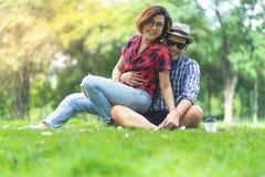 Женское усаживание на подоле человека в зеленом парке, счастливой паре стоковое фото