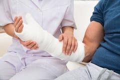 Женское удерживание доктора сломало руку пациента Стоковая Фотография RF