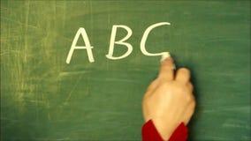 Женское ` ABC ` сочинительства руки на доске и чертеже smiley под письмами сток-видео