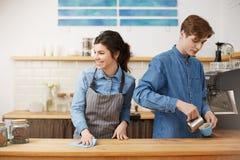 Женское barista моя губкой вниз с таблицы усмехаясь счастливо Кофе Make лить Стоковые Фотографии RF
