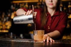 Женское mixoligist лить свежее питье от шейкера в стекло стоковые фотографии rf