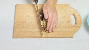 Женское ` s шеф-повара вручает прерывать смешанные гайки на деревянной разделочной доске акции видеоматериалы