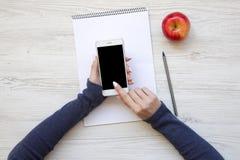 Женственное место для работы с smartphone, тетрадью и яблоком Взгляд сверху стоковое изображение