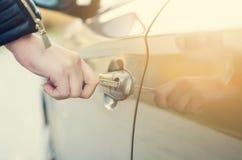 женщина автомобиля ключевая Автомобильная дверь отверстия Рука Womanоткрывая дверь на автомобиле sunlight перевозка Стоковая Фотография