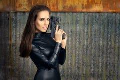 Женщина агента шпионки в черном кожаном костюме держа оружие Стоковые Фотографии RF