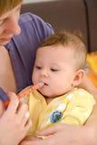 Женщина дает к больной медицине младенца посредством batcher стоковая фотография