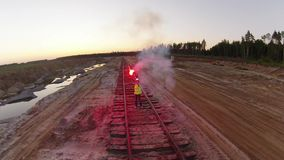 Женщина дает сигнал СТОПА для поезда с красным пирофакелом сток-видео