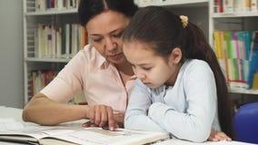 Женщина азиата зрелая читая книгу с ее милой дочерью litlle стоковое фото