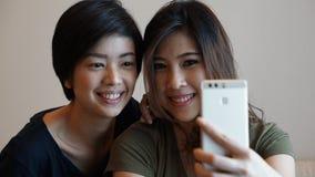Женщина 2 азиатов принимая фото, selfie используя сотовый телефон Стоковое фото RF