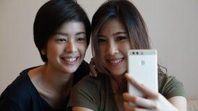 Женщина 2 азиатов принимая фото, selfie используя сотовый телефон Стоковые Фото