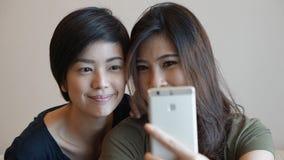 Женщина 2 азиатов принимая фото, selfie используя сотовый телефон Стоковые Фотографии RF