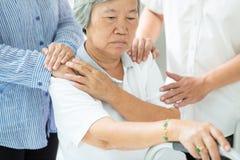 Женщина азиатской семьи утешая подавленная старшая; грустному престарелому с упадочными симптомами нужна близкая забота; руки на  стоковая фотография