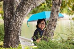 Женщина Азии держа зонтик в парке Стоковые Фото