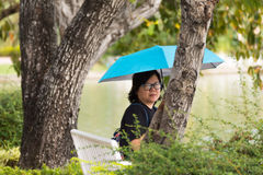 Женщина Азии держа зонтик в парке Стоковое фото RF
