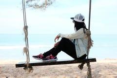 Женщина Азии сидя самостоятельно на деревянной веревочке стула на пляже смотря t Стоковые Изображения RF