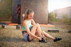 Женщина альпиниста утеса сильная кладя на взбираясь ботинки пока сидящ на траве Довольно здоровая тонкая девушка подготавливает д Стоковое Фото