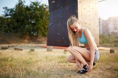Женщина альпиниста утеса сильная кладя на взбираясь ботинки пока сидящ на траве Довольно здоровая тонкая девушка подготавливает д Стоковая Фотография RF
