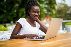 Женщина американца Афро молодая черная курчавая сидит в кафе и имеет удаленную работу используя ноутбук стоковое изображение